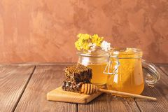 Fresh fragrant honey in a glass jar on a wooden background on the table. Different types of bee honey. Natural products. Fresh fragrant honey in a glass jar on royalty free stock photography