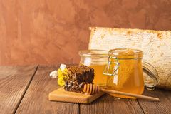 Fresh fragrant honey in a glass jar on a wooden background on the table. Different types of bee honey. Natural products. Fresh fragrant honey in a glass jar on stock photos