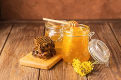 Fresh fragrant honey in a glass jar on a wooden background on the table. Different types of bee honey. Natural products. Fresh fragrant honey in a glass jar on stock photo
