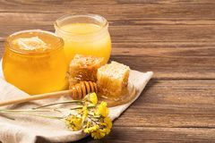 Fresh fragrant honey in a glass jar on a wooden background on the table. Different types of bee honey. Natural products. Fresh fragrant honey in a glass jar on royalty free stock images