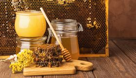 Fresh fragrant honey in a glass jar on a wooden background on the table. Different types of bee honey. Natural products. Fresh fragrant honey in a glass jar on royalty free stock image