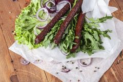 Fresh fragrant salad with sausages, onions, arugula and lettuce. Leaves. Delicious and raw food. Healthy food. Meat and natural dishes. Meat dish Royalty Free Stock Photos