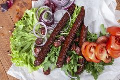 Fresh fragrant salad with sausages, onions, arugula and lettuce. Leaves. Delicious and raw food. Healthy food. Meat and natural dishes. Meat dish Stock Photo