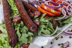 Fresh fragrant salad with sausages, onions, arugula and lettuce. Leaves. Delicious and raw food. Healthy food. Meat and natural dishes. Meat dish Stock Images