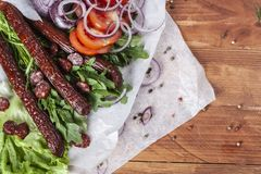 Fresh fragrant salad with sausages, onions, arugula and lettuce. Leaves. Delicious and raw food. Healthy food. Meat and natural dishes. Meat dish Royalty Free Stock Photography