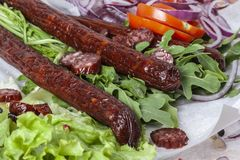 Fresh fragrant salad with sausages, onions, arugula and lettuce. Leaves. Delicious and raw food. Healthy food. Meat and natural dishes. Meat dish Stock Photos