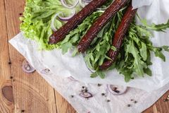 Fresh fragrant salad with sausages, onions, arugula and lettuce. Leaves. Delicious and raw food. Healthy food. Meat and natural dishes. Meat dish Stock Image