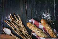 Fresh french baguette bread, organic flour and wholegrain wheat on dark vintage wooden board form above