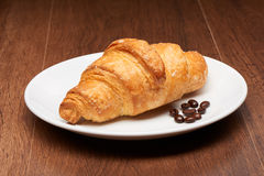 Fresh french croissant and coffee beans on white ceramic plate on dark wooden table Royalty Free Stock Photos
