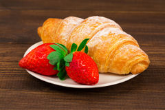Fresh french croissant and strawberry on brown wooden table background Stock Photography