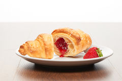 Fresh french croissant with strawberry jam filling cut into two pieces and strawberry on white ceramic plate on bright light brown Stock Photo