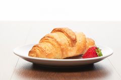 Fresh french croissant and strawberry on white ceramic plate on bright light brown wooden table Royalty Free Stock Photography