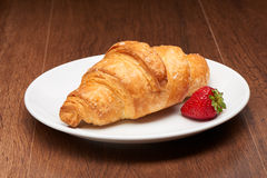 Fresh french croissant and strawberry on white ceramic plate on dark wooden table. Background Stock Photo
