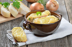Fresh French onion soup. French onion soup with baked cheese baguette in a brown bowl Stock Photo