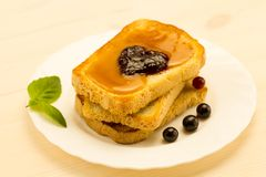 Fresh french toast with honey and jam on a white plate with berries. Royalty Free Stock Images