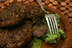 Fresh fried burgers. On wooden plate Stock Photography