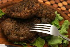 Fresh fried burgers and fork. Fresh fried burgers on plate with fork Royalty Free Stock Images