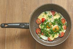 Fresh fried eggs are cooked in a frying pan, with tomatoes, cheese and greens. Vegetarian dishes. Bright healthy food on a wooden stock photos