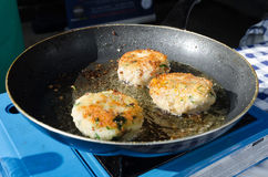 Fresh fried fish cakes pan frying in the sunlight Stock Photos