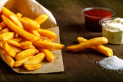Fresh fried french fries with ketchup on wooden background Stock Photography