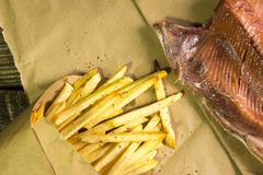Fresh fried French fries and salmon on wooden background. A textured background.Copy paste place stock photo