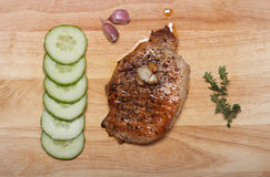 Fresh fried meat with thyme, garlic and cucumber on light wooden Stock Photo