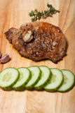 Fresh fried meat with thyme, garlic and cucumber on light wooden Royalty Free Stock Images