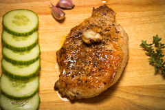 Fresh fried meat with thyme, garlic and cucumber on light wooden Royalty Free Stock Image