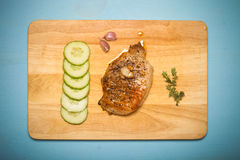 Fresh fried meat with thyme, garlic and cucumber on light wooden Stock Photography
