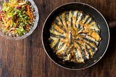 Fresh Fried Sardines in Pan with Salad on Wooden Surface. Seafood Concept Royalty Free Stock Photo