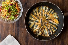 Fresh Fried Sardines in Pan with Salad on Wooden Surface. Seafood Concept Stock Image
