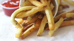 Fresh Fries hand dips chip in tomato sauce. Chips on paper napkin stock video footage