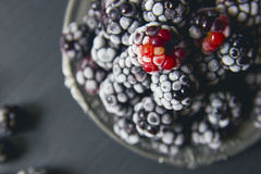 Fresh frozen blackberries on a black stone kitchen table.  Stock Photos