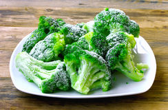 Fresh frozen broccoli on white plate. Wooden table, healthy diet food, closeup Royalty Free Stock Photo