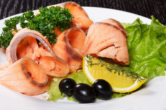 Fresh-frozen fish slices with vegetables. Slices of red fish with lemon and olives on plate Stock Image