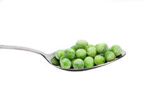 Fresh frozen green peas on spoon Stock Images