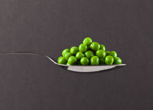Fresh frozen peas on spoon Royalty Free Stock Images