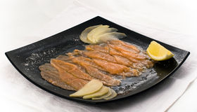 Fresh-frozen salmon slices. On a black plate Stock Photo