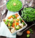 Fresh frozen vegetables on wooden background close up stock photo