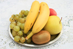 Fresh fruit. Photo of a plate with bananas, apples, kiwi and grapes Royalty Free Stock Photo
