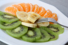 Fresh fruit. Healthy plate composed of  fresh kiwi, tanguerine and banana aporting a lot of vitamines Royalty Free Stock Image