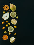 Fresh fruit andcitrus mix on black: pieces of pear, mandarin; gr Royalty Free Stock Image