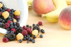 Fresh fruit and berries. A cutting board full of fruit waiting to become a salad or desert, it consists of peaches, bananas,blueberries,blackberries,red royalty free stock image