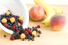 Fresh fruit and berries. A cutting board full of fruit waiting to become a salad or desert, it consists of peaches, bananas,blueberries,blackberries,red royalty free stock images