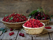 Fresh fruit and berries in baskets on wooden background. Currants, raspberries, cherries royalty free stock photos