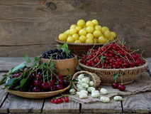Fresh fruit and berries in baskets on wooden background. Fresh fruits and berries in the basket on wooden background - cherry, red and black currant, yellow plum royalty free stock photos