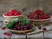 Fresh fruit and berries in baskets on wooden background. Fresh fruits and berries in the basket on wooden background - raspberry, cherry, plum red currant royalty free stock photography