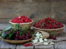 Fresh fruit and berries in baskets on wooden background. Raspberry, cherry, red currant, white mulberry stock image