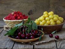 Fresh fruit and berries in baskets on wooden background. Raspberry, cherry, yellow plum royalty free stock image