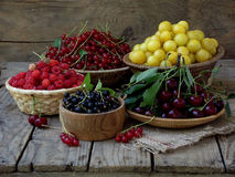 Fresh fruit and berries in baskets on wooden background. Red and black currants, raspberries, cherries, yellow plums stock photo